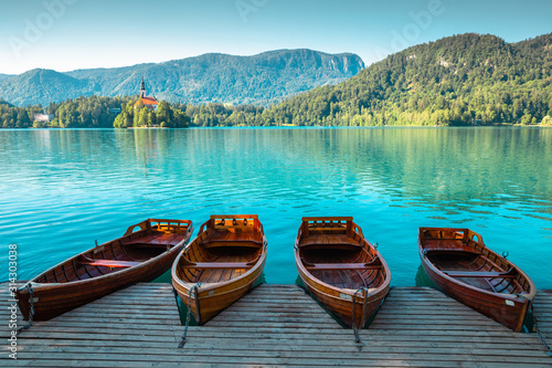 Lake Bled, wooden boats and pilgrimage church of the assumption of maria in Slov Fotobehang
