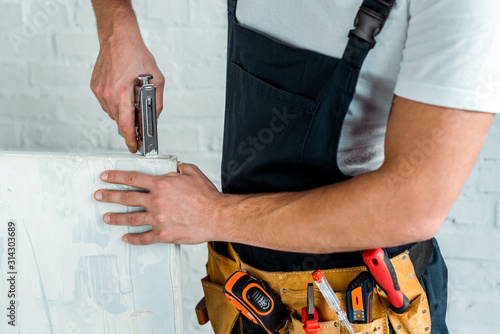 cropped view of installer holding construction stapler near painting