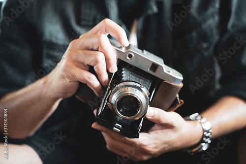 Fototapeta a man holding the vintage old film camera   obraz na płótnie