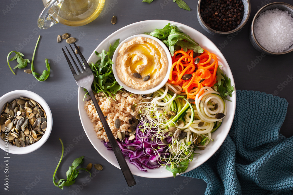 Fototapeta veggie couscous lunch bowl with spiralazed carrots and zucchini, hummus and red cabbage