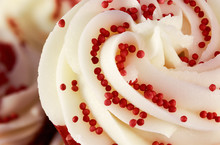 Closeup Of Red Velvet Cupcake Decorated With Swirled Icing And Sugar Beads