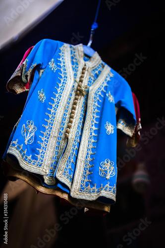 Dziecko djellaba w sklepie kupca w suku medyny Fez w Maroku