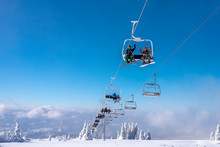People Enjoying Winter Sports. Skiers On Chairlift At Mountain Ski Resort