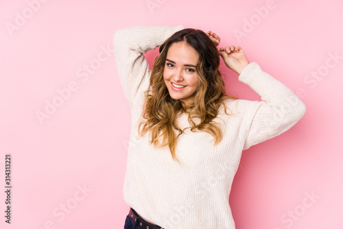 Obraz Young curvy woman posing in a pink background isolated stretching arms, relaxed position. - fototapety do salonu