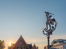 Statue Of Archangel Saint Michael Slaying A Dragon Next To Promenade Of River Lys In Ghent, Belgium And At Dusk. Gent Old Town Is Famous Iron Cast Sightseeing Spot.