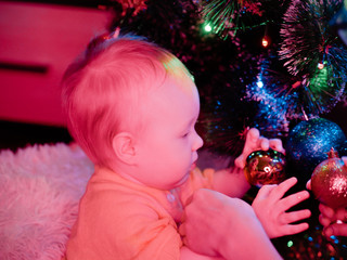 Baby with toys on the background of the Christmas tree