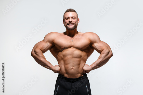 Fotografie, Obraz Young muscular bodybuilder guy demonstrates his muscles isolated on a light gray background