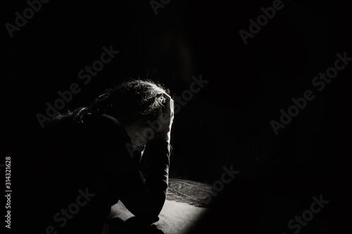 Cuadros en Lienzo lonely and sad girl holding her head on a black background