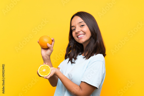 Young brunette girl holding an orange Tablou Canvas