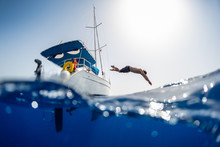 Young Man Jumps Into The Sea From The Sail Boat, Splitted Over Under Image With The Crystal Clear Sea