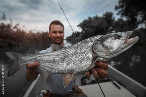Angler holds big Asp fish and smiles Canvas Print