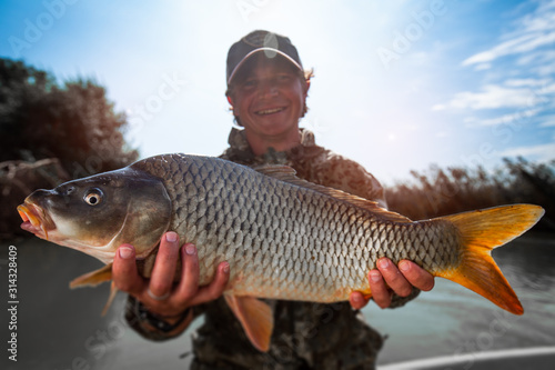 Obraz Happy fisherman holds the big Carp fish (Cyprinus carpio) and smiles - fototapety do salonu