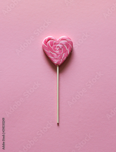 Lollipop różowy kształt serca na różowym tle. Walentynki kartkę z życzeniami