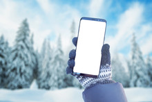 Phone Mockup In Hand With Gloves. Winter, Cold Time With A Lot Of Snow In Mountain. Isolated Screen For Mockup, App Promotion. Snowy Trees In Background