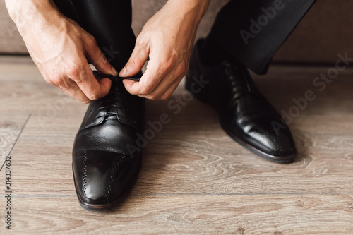 Photo Frontview of man is tying the laces at black shoes on the wooden floor