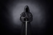 canvas print picture - Ghostly figure with medieval sword in the dark