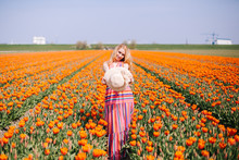 Magical Landscape With Beautiful Young Long Red Hair Woman Wearing On Striped Dress And Straw Hat Standing On Colorful Flower Tulip Field In Holland. Dutch Girl In Tulips Fields In Netherlands.