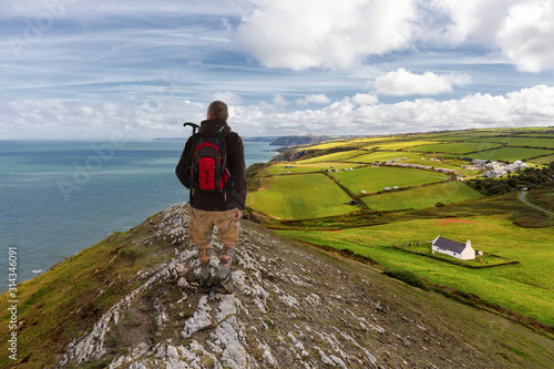 Fototapeta A hiker on the coastal path in Wales. The man looks at the sea. Below is the green land and a small white chapel. A cool and sunny day with a blue sky. obraz
