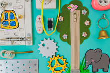 Colorful Busy Board As Best Toy For Kids. Wooden Board With Zipper, Velcro, Flashlight, Mirror, Switch, Chain And Beeds For Small Kids Fingers. Best Toy For Parrents Rest.