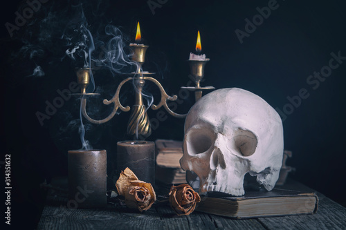 Fotografie, Obraz Skull, burning candles, a book and two dry roses on a  dark background