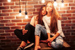 canvas print picture - two teenage girl friends together having fun in modern loft interior with holiday lights, lifestyle people concept