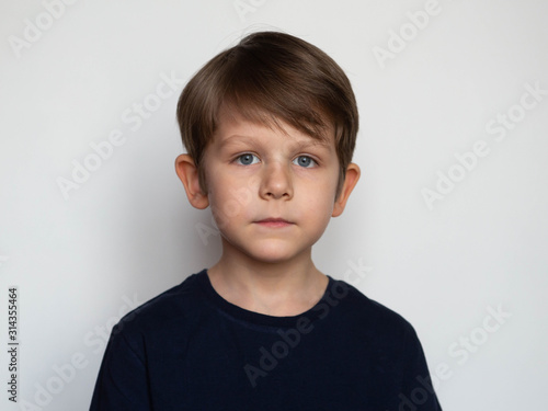 Obraz Portrait of a serious little boy on a white background - fototapety do salonu
