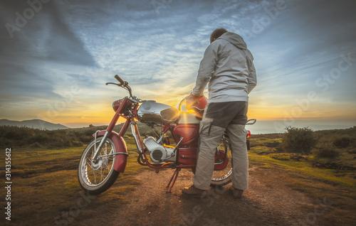 Fotografia, Obraz  Homem junto a moto antiga a ver o pôr do sol