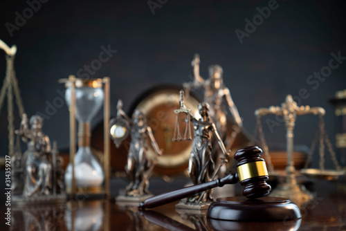 Obraz Law and justice theme. Judge's gavel, Themis statue,  scale, hourglass and old clock on the shining wooden brown table and the gray background. - fototapety do salonu