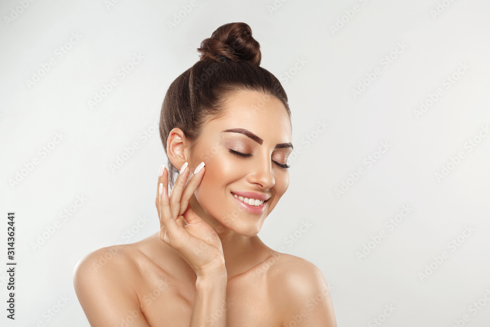 Fototapeta Beautiful young woman with clean perfect skin. Portrait of beauty model with natural nude make up and touching her face. Spa, skincare and wellness. Close up, copyspace.