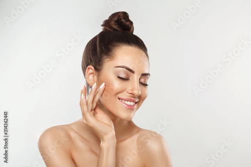 Beautiful young woman with clean perfect skin. Portrait of beauty model with natural nude make up and touching her face. Spa, skincare and wellness. Close up, copyspace.
