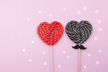 Valentine's day. The concept of a lover. Red and black Lollipops in the shape of a heart and confetti of stars on a pink background. Top view. Copy space.