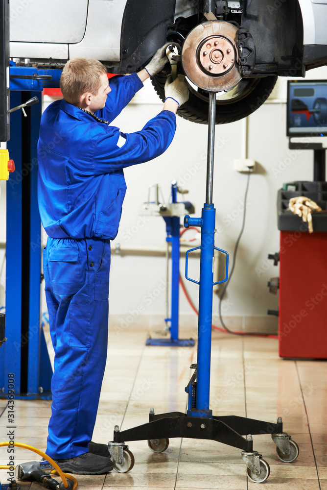 Fototapeta Auto repair service. Mechanic inspecting car brakes and pads