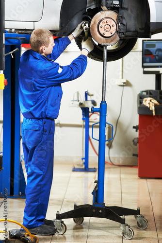 Fototapeta Auto repair service. Mechanic inspecting car brakes and pads obraz