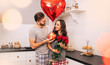 For you, my dear. A nice man in house clothing is giving roses and presents to his wife on Valentine's Day. A couple is smiling while celebrating together at home.