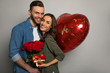 The day of romance. Close up photo of a happy couple, who are hugging, smiling and holding a bouquet of roses, a red balloon, and a present box, celebrating their anniversary.