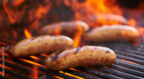 Fototapeta tasty bratwurst sausage barbecuing on the grill obraz
