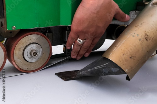 Photo mechanism for laying and gluing sheets of roofing polymer