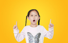 Excited Little Asian Child Girl Pointing Two Forefinger Up Isolated Over Yellow Background.