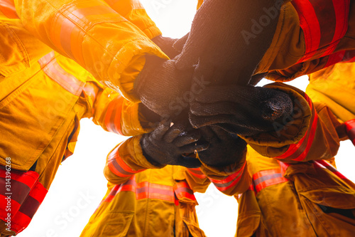 Firefighter putting hands up for fire fighting, Cheerful people giving strength motivation Fototapet