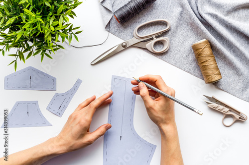 Obraz Tailor working. Women hands make patterns for clothes on white background top-down - fototapety do salonu