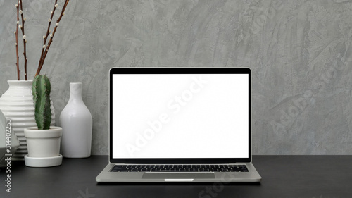Fototapeta Cropped shot of modern workspace with blank screen laptop and ceramic vase on black desk with grey loft wall obraz