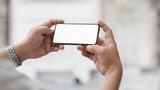 Fototapeta Kawa jest smaczna - Cropped shot of  businessman holding horizontal blank screen smartphone with blurred office room