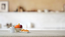 Close Up View Of Fruit Bowl, Coffee Cup And Croissant On Marble Desk With Blurred Kitchen Room