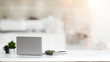canvas print picture - Close up view of simple workspace with laptop, notebooks, coffee cup and tree pot on white table with blurred office room