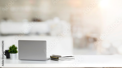 Obraz Close up view of simple workspace with laptop, notebooks, coffee cup and tree pot on white table with blurred office room - fototapety do salonu