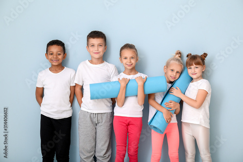 Fototapeta Little children with yoga mats near color wall obraz