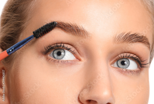 Canvas-taulu Young woman undergoing eyebrow correction procedure, closeup