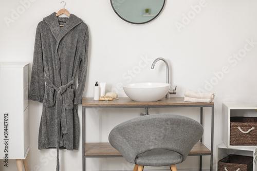Clean bathrobe hanging on wall indoors Fototapeta