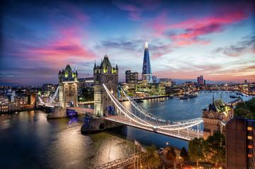 Blick auf die Tower Brücke und die Skyline von London mit den beleuchteten Hochhäusern an der Themse nach Sonnenuntergang, Großbritannien