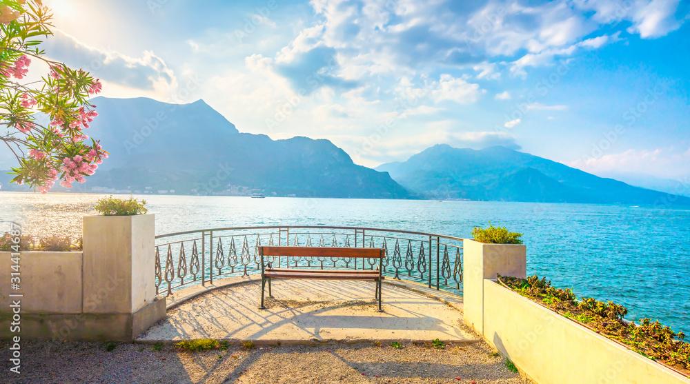 Fototapeta Bench on lakefront in Como Lake landscape. Bellagio Italy